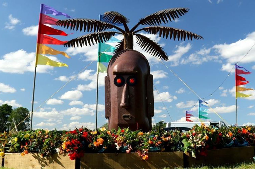 Giant head sculpture and flags at FolkEast