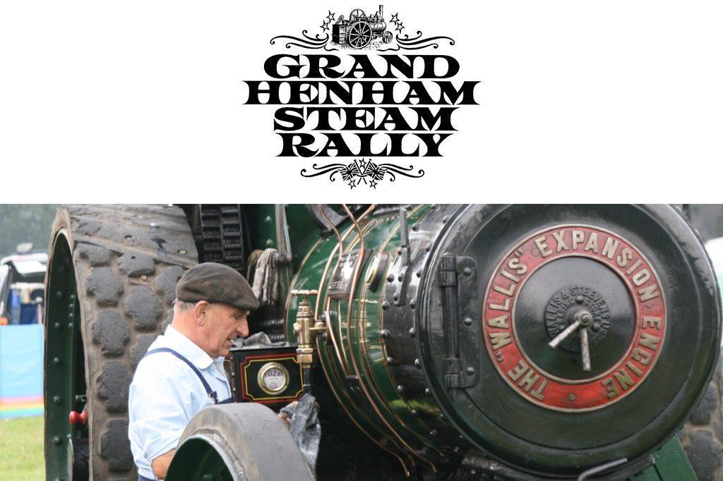 Henham steam rally logo and man stood in front of steam engine