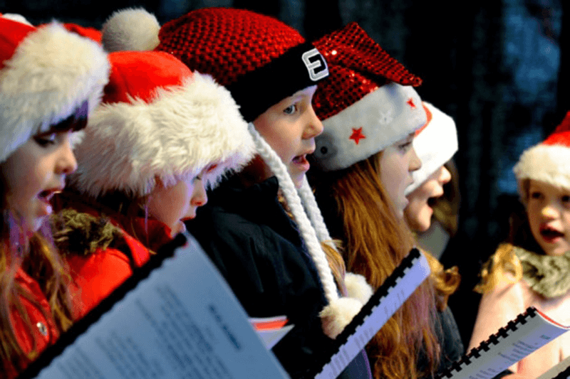 Children sing carols in Christmas hats